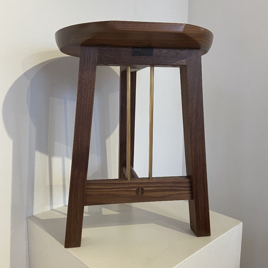 Buy 'Trio Stool' a handmade dark wood stool by Majid Lavasani. Image shows a dark wood round stool with 3 legs and brass posts sat on a rounded plinth against a white wall.