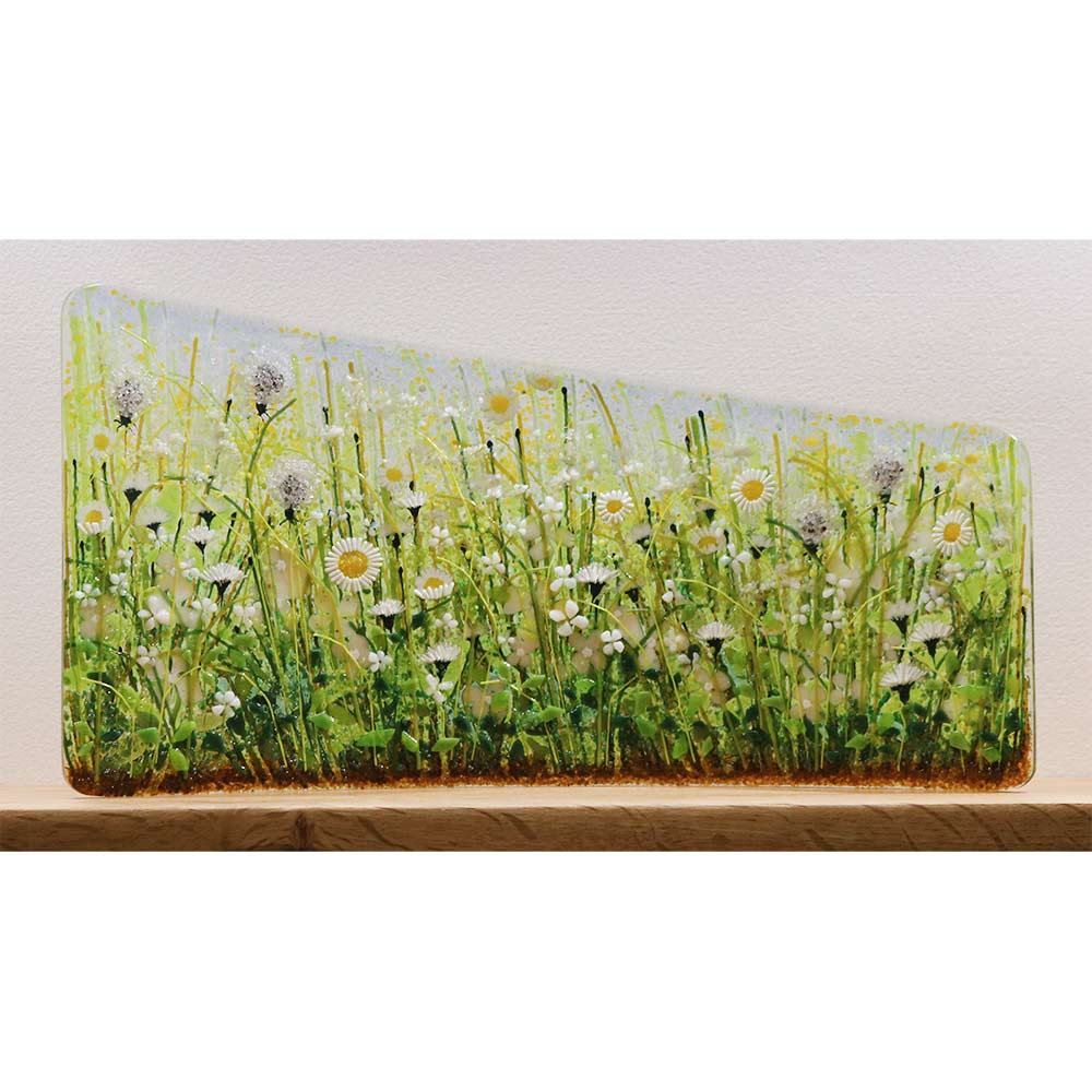 Buy 'White Meadow Asymmetric Curve' a handmade glass sculpture by Vandacrafts. Image shows a curved glass panel shorter in height on the left side than the right. The panel is decorated with a floral meadow scene with thistles, daisies and grass - predominately white and green in colour. The sculpture sits on a wooden shelf on a white background.