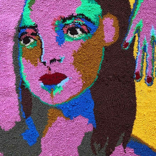 'Why do you rather it than me?', a tapestry wall hanging by textile artist Selby Hurst Inglefield. Image shows a tapestry portrait of a bold multicolored person with long brown hair and bold their arm reaches over their head. The background is bright yellow