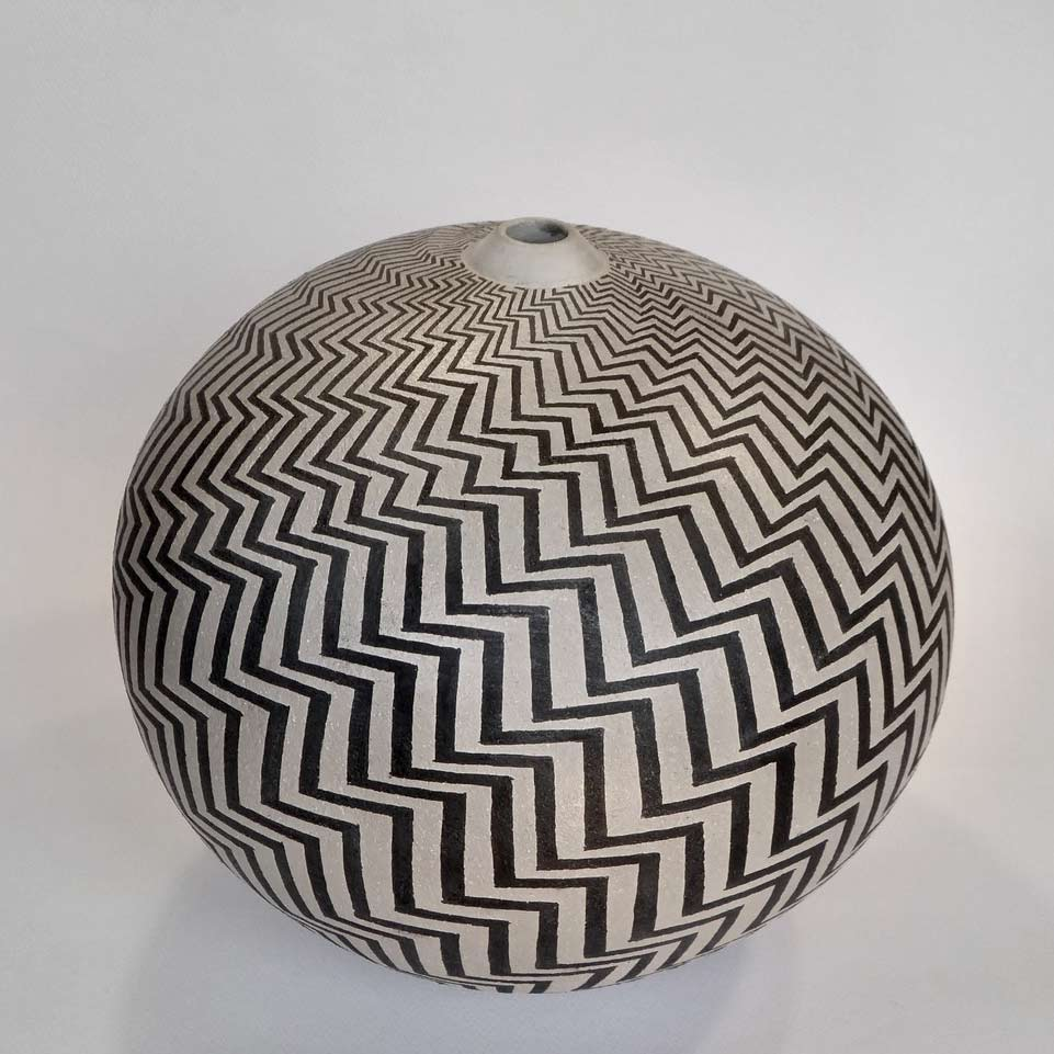 Buy 'Zigzag' a large ceramic vessel by Ilona Sulikova. Image shows a spherical ceramic pot with a very narrow lipped opening at the top decorated with black zigzag lines that spiral out from the top of the pot and wrap around, widening and narrowing around its form.