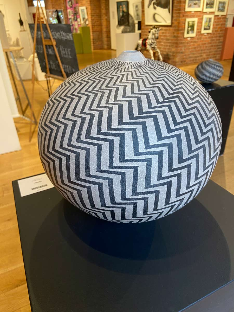 Buy 'Zigzag' a large ceramic vessel by Ilona Sulikova. Image shows a spherical ceramic pot with a very narrow lipped opening at the top decorated with black zigzag lines that spiral out from the top of the pot and wrap around, widening and narrowing around its form. The pot sits on a black plinth on a pine gallery floor. Behind it are various indistinguishable sculpture and paintings on brick walls and multicoloured plinths
