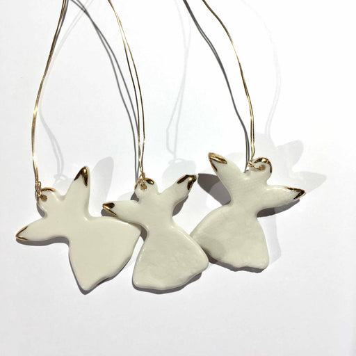 Buy 'Angel Christmas Decoration', a ceramic tree ornament by Kirsty Adams. Image shows three cream ceramic angel silhouettes printed with a lace texture and tipped with gold details lay flat on a white surface.