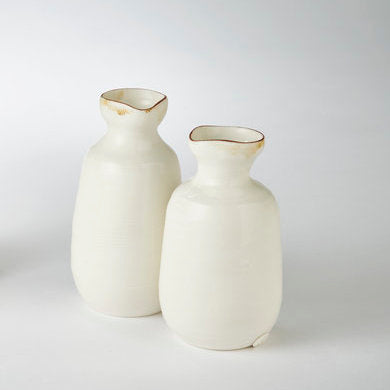Buy 'Oil Pourer, a ceramic jug by Kirsty Adams. Image shows two cream ceramic pourers with pinched necks and bronze washed rim. They sit on a pale grey background.
