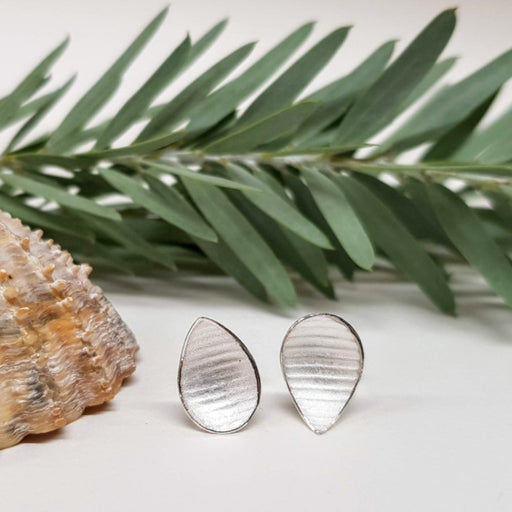 View and buy ethical handmade jewellery online at The Biscuit Factory. 'Small Pyrus Earrings' silver floral studs by Donna Barry. Image shows a pair of stripe-textured silver teardrop studs sat on a white surface with a green leafy branch in the background and a large shell to the left