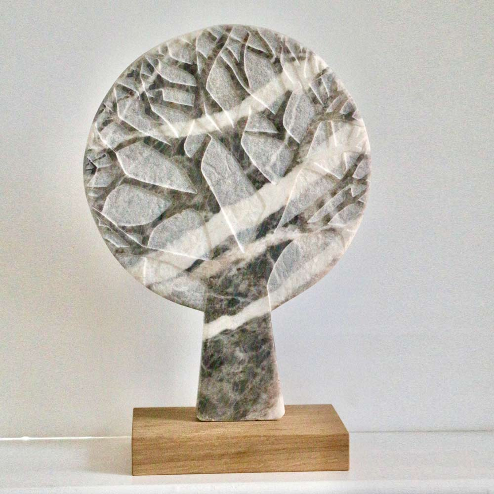 Buy 'Winter Tree in the Clouds', a marble sculpture by Michael Disley. Image shows a circular paddle shaped marble sculpture in grey with a darker grey skeletal tree etched into it, sat on a wooden block plinth. The background is white.