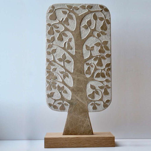 Buy 'Tall Pear Tree', a marble sculpture by Michael Disley. Image shows a rectangular paddle shaped marble statue n beige etched to reveal a pear tree sat on an oak plinth. The background is white.