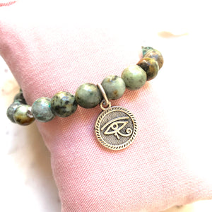Aria Mala Atelier's unique one-of-a-kind African Turquoise, Natural Sandalwood RA (Eye of Horus) Charm yoga bracelet for spiritual living