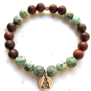 Aria Mala Atelier's unique one-of-a-kind African Turquoise, Natural Sandalwood yoga bracelet with RA, Yoga, OM charm for spiritual living