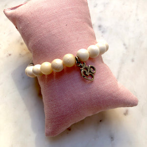 Aria Mala Atelier's unique one-of-a-kind shell stone yoga bracelet with sterling silver OM charm for spiritual living