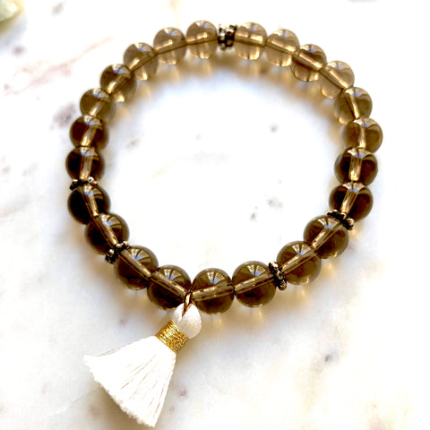 Aria Mala Atelier's unique one-of-a-kind smoky quartz yoga bracelet with mini cotton tassel for spiritual living