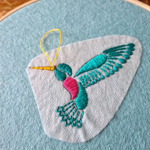 a close up of a hand embroidered turquoise hummingbird, stitched onto turquoise green felt with transfer paper