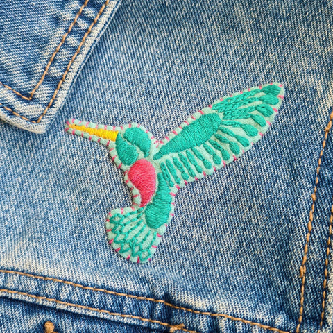 an embroidered patch showing a hummingbird design, attached to a denim jacket with pink thread.