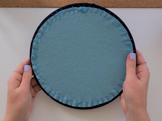 The reverse of an embroidery hoop backed with teal felt