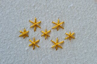 Six embroidered yellow stars on white fabric background