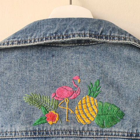 A denim jacket is on a hanger against a white wall. The back of the jacket shows a hand embroidered design of a flamingo, pineapple, flower, and monstera leaf
