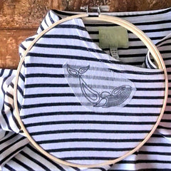 A striped shirt is inside a large embroidery hoop. A piece of paper showing a whale design has been stuck to the neckline of the shirt.