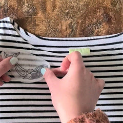 A striped t-shirt is lying on a wooden table. A pair of hands are holding a small piece of paper showing a whale design, sticking it to the shirt