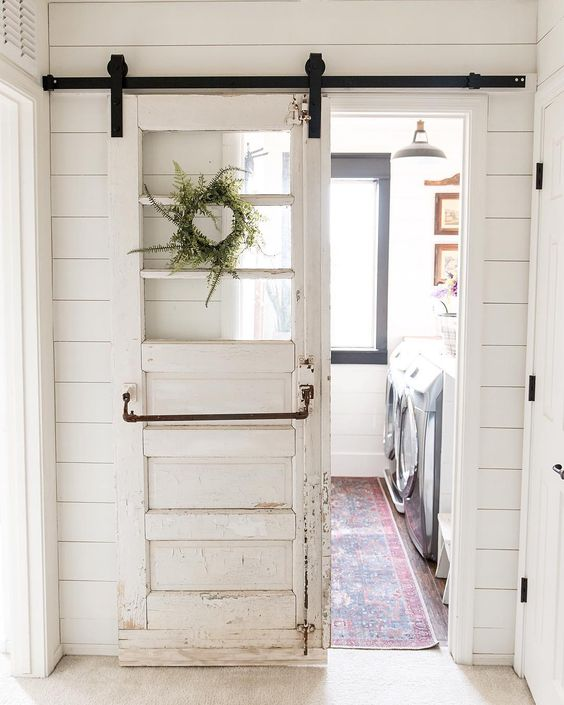 barn door to laundry room made with salvaged gymnasium door