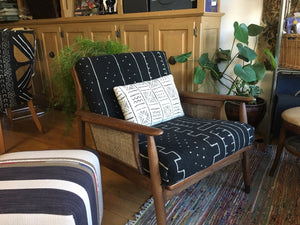 white mali mudcloth pillow on black mali mudcloth upholstered danish chair in miller upholstering shop
