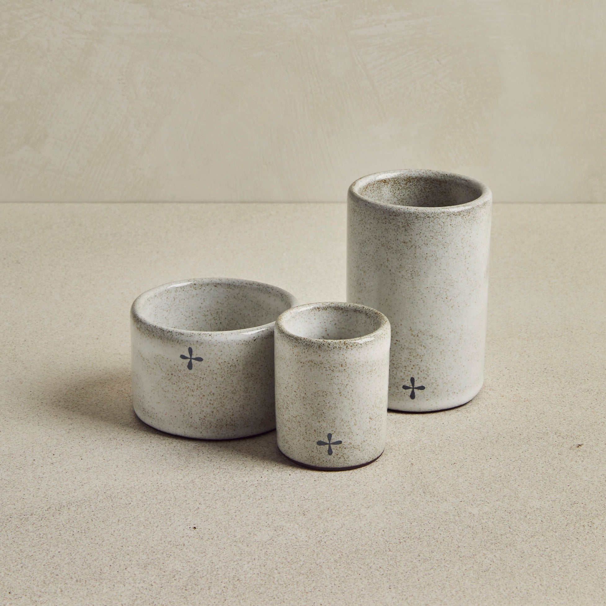 trio of grey ceramic glasses on a beige background