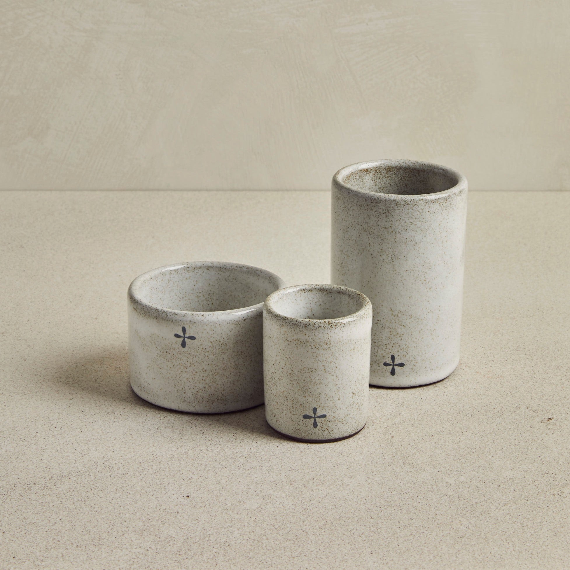Trio of empty grey ceramic cups, on a beige background