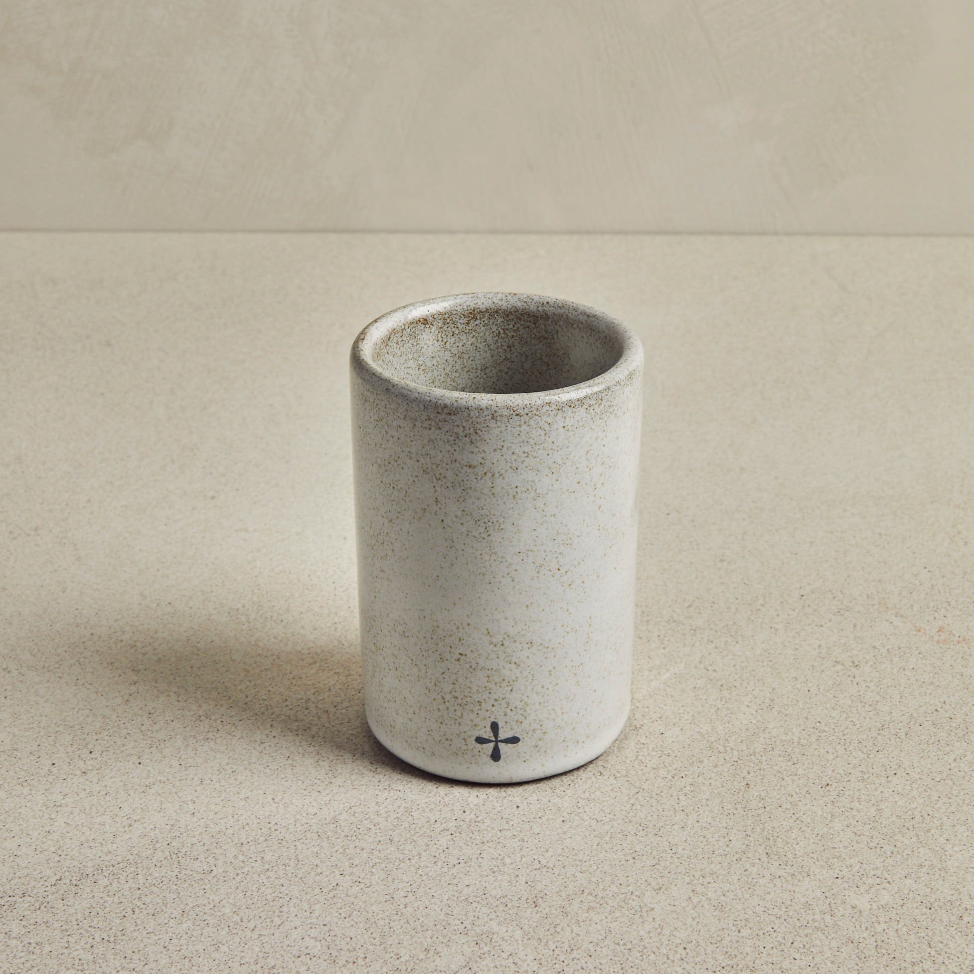Ceramic grey cylindrical glass on beige background