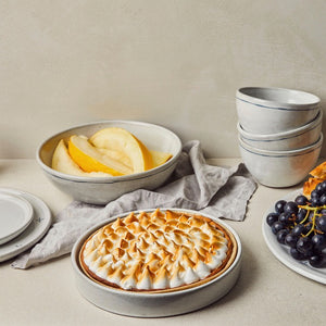 Tableware set with pie with bowl of fruit, and packed bowls