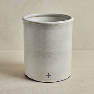 Large light gray cylindric bin, on beige background