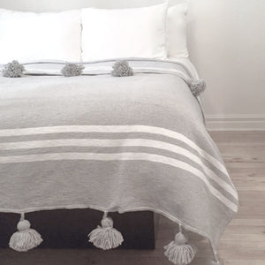 couverture grise à rayures avec pompons gris sur lit, gray striped banket with gray pompons on a bed