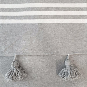gray pompoms on a gray striped cotton material, pompons gris sur tissus gris rayé