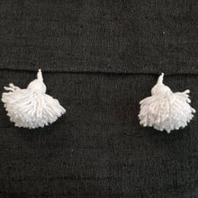 white pompoms on black cotton material, pompons blancs sur tissus de coton noir