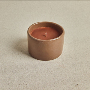 Candle with colored ceramic container, orange with beige background