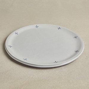 Large solid gray ceramic platter, with patterns on the circumference, on beige background