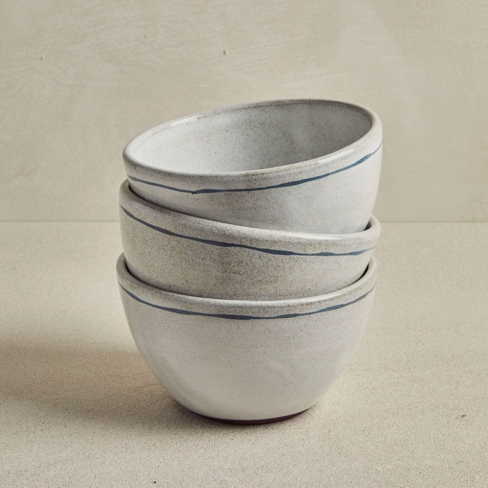 3 Grey bowls with anthracite line stacked, on beige background