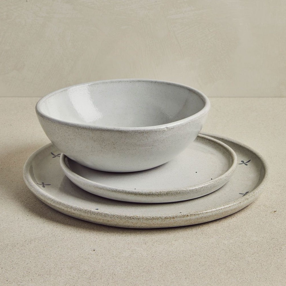 Trio of grey dishes stacked on a beige background
