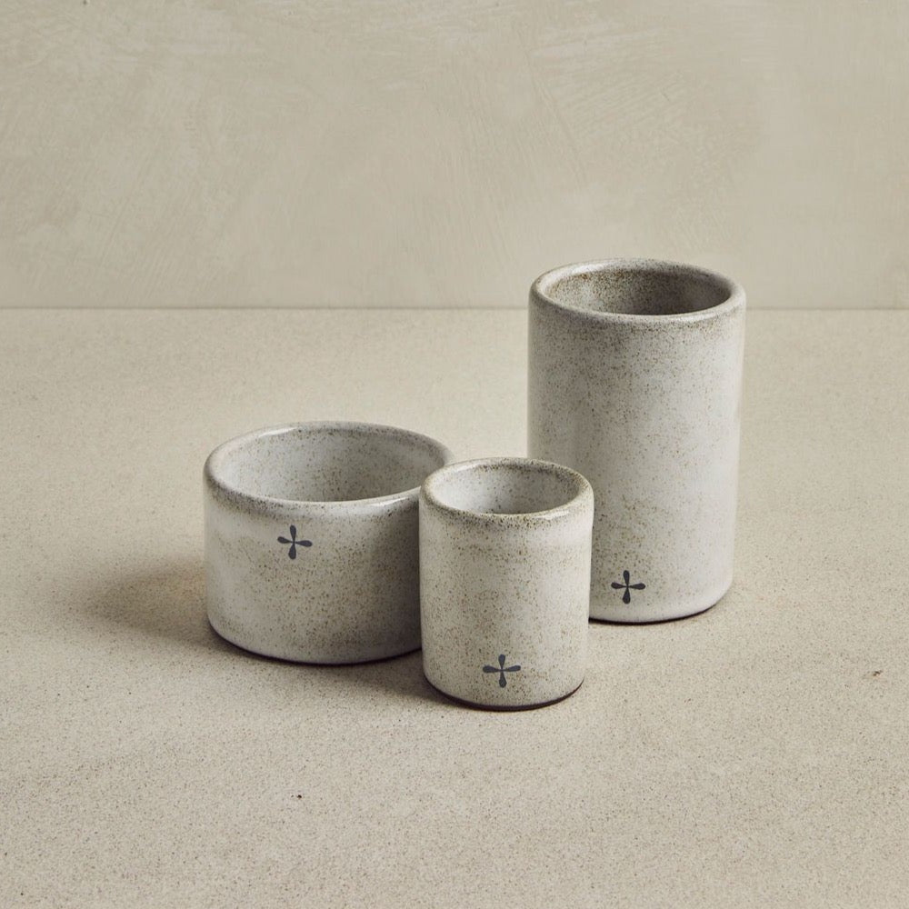 Three Light gray ceramic ramekin on a beige backgroung