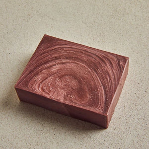 Pink soap block with textures on a beige background