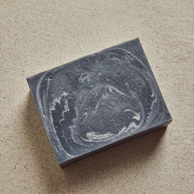 Anthracite bar soap marbled on a beige background