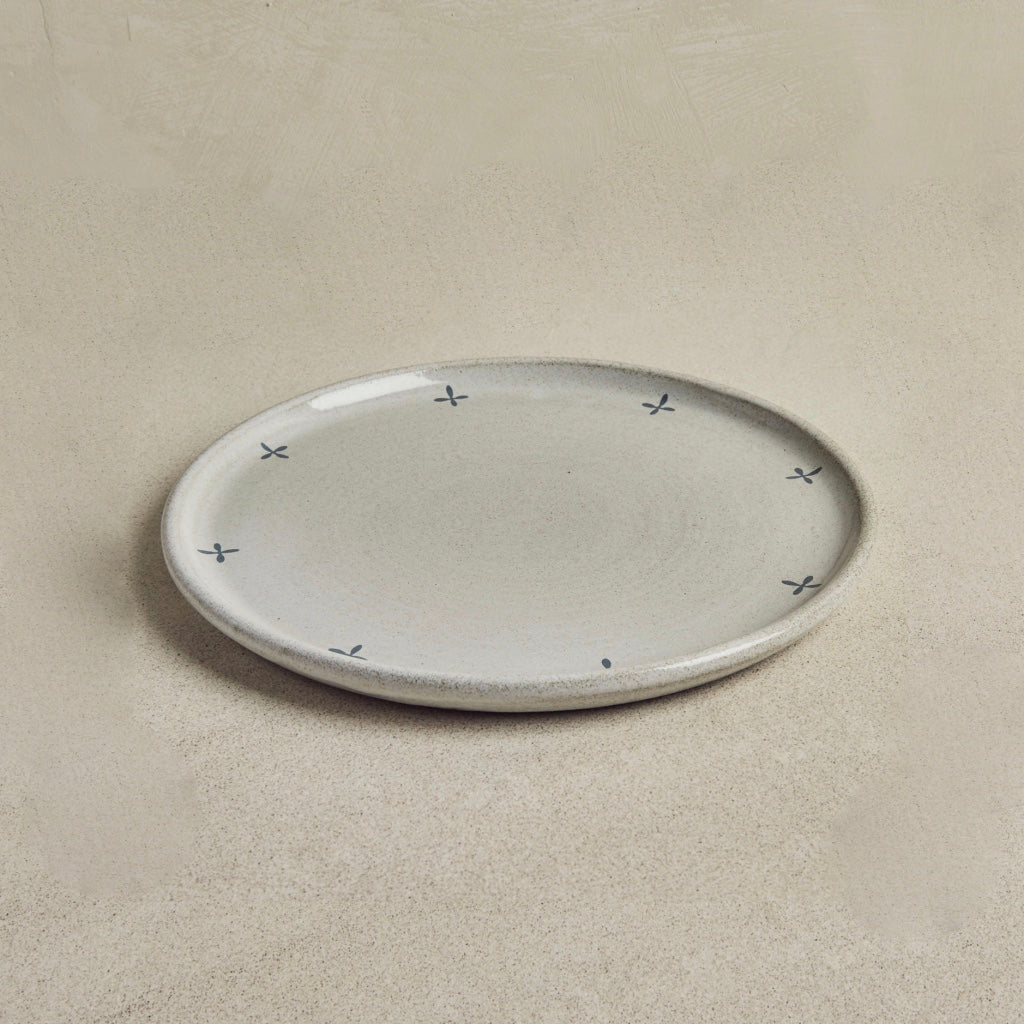 Grey plate with simple anthracite patterns on beige background