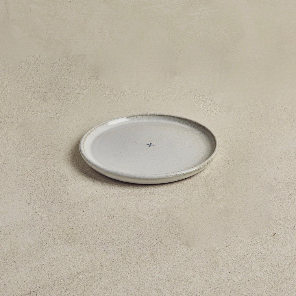 Light gray ceramic plate on beige background