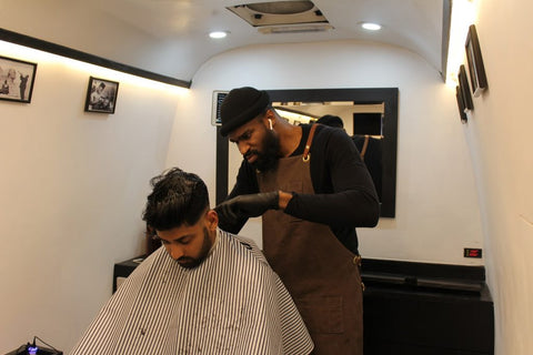 Photo of a man doing haircut to another a man