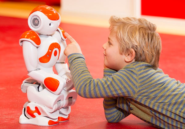 Photo of a child playing with a humanoid robot