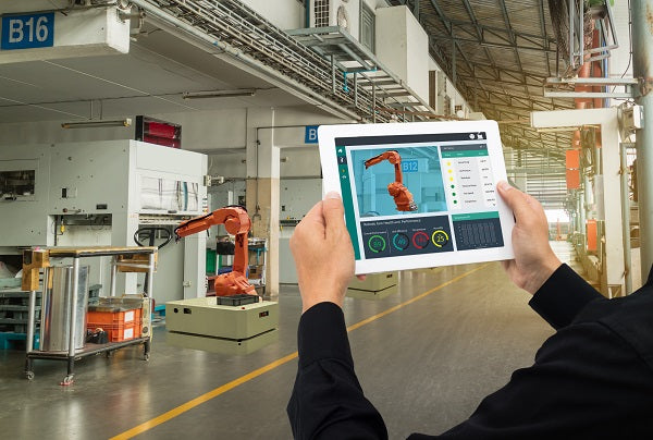 Photo of industrial engineer using the software on a tablet to monitoring robot arm in automotive manufacturing