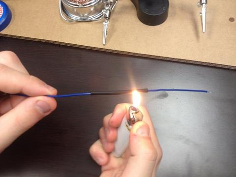 Photo of arm's of a man holding lighter and wire