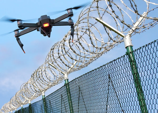 Photo of a drone near a wire fence in a restricted access area
