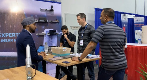 Photo of four men communicating at the ATX West show in USA