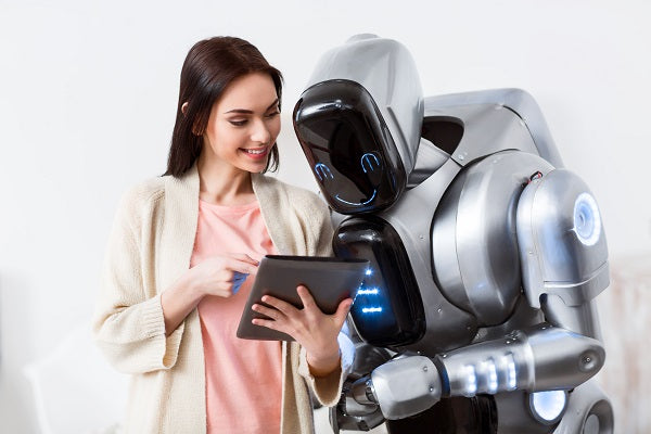 Photo of a beautiful girl holding tablet and showing it to the robot