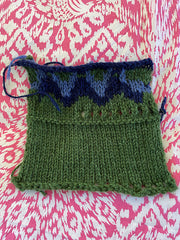 Swatch of both solid green stockinette and color work with dark and light blue.