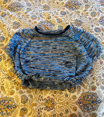 The top of a half finished sweater out of blue and gray variegated yarn