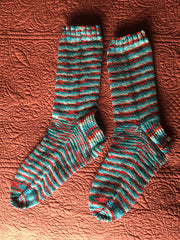 Two finished, striped socks in teal and red.